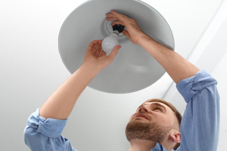 mies vaihtaa lamppua kattovalaisimeen